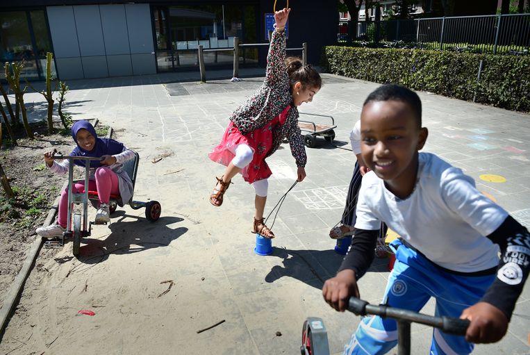 Tijdens de pauze stroomt het schoolplein vol met kinderen die druk door elkaar heen rennen en op skelters rijden. Beeld Marcel van den Bergh / de Volkskrant