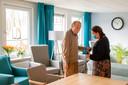 """Teamleider Nathalie Quint helpt Gerrit Siermans, bewoner van het Henriëtte van Heemstrahuis van Bartiméus in Ermelo. Siermans heeft een visuele beperking. ,,We kunnen geen oogcontact maken, daarom is een aanraking zo belangrijk."""""""