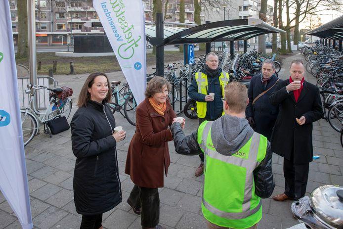 Wethouder Engbert Stroobosscher (helemaal rechts) deelt in 2019 chocomel en koekjes uit tijdens de opening van een nieuwe fietsenstalling bij het station Veenendaal Centrum.