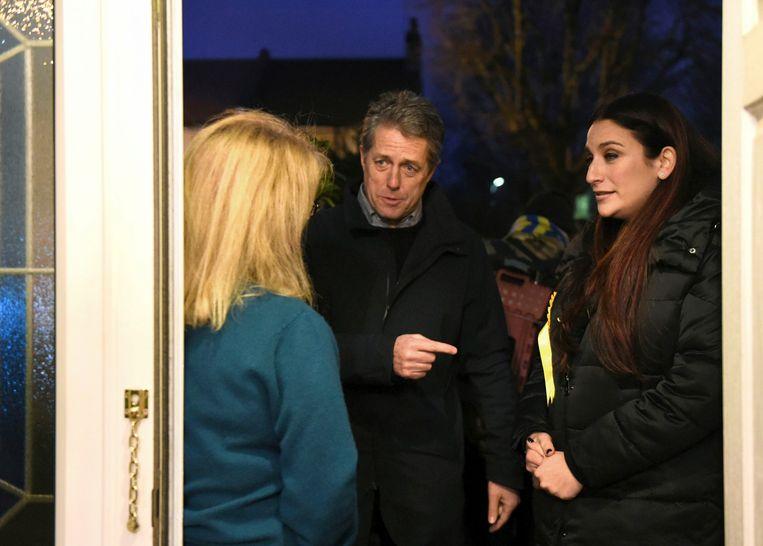 Acteur Hugh Grant gaat met de Lib-Dem-kandidaat Luciana Berger van deur tot deur. Beeld AP