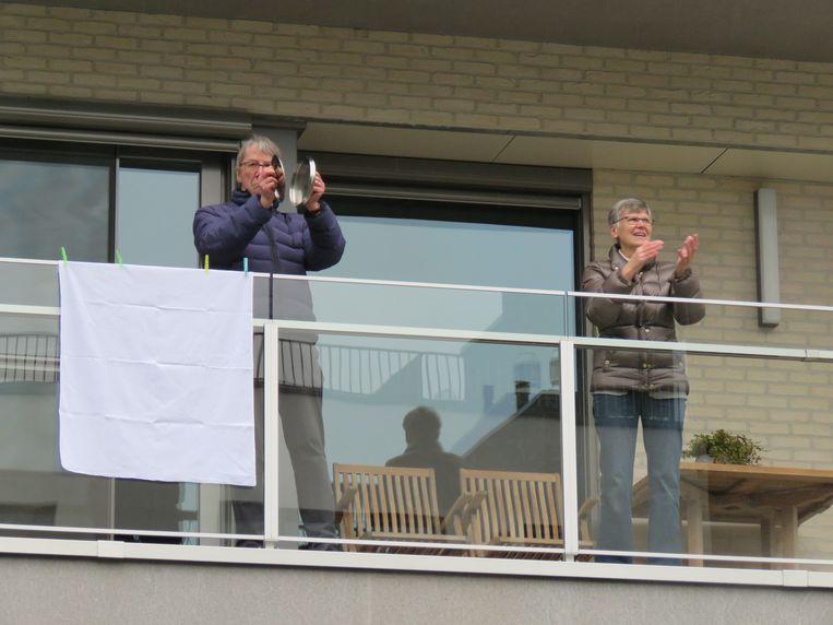 Applaus en witte lakens voor de zorgverleners op De Munt.