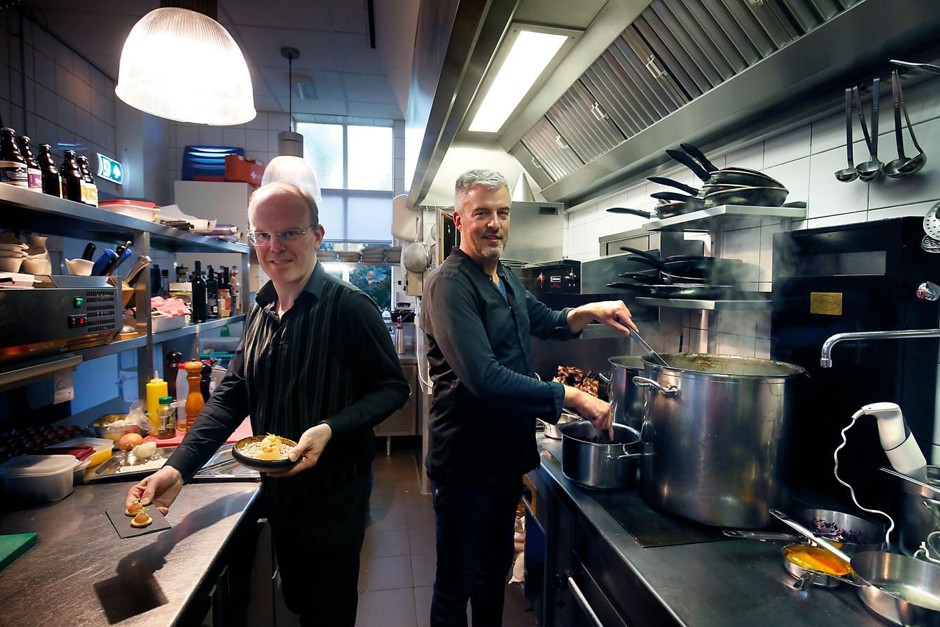 Gastheer-sommelier Michaël (links) en chef en eigenaar Patrick (rechts) in de open keuken van het restaurant.