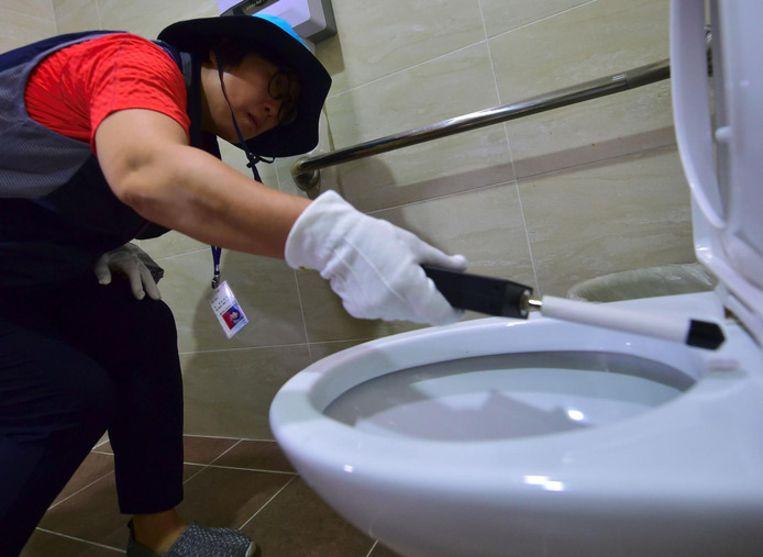 Een lid van de 'verborgen camera jagers' haalt een detector langs een toilet om verborgen camera's te vinden.