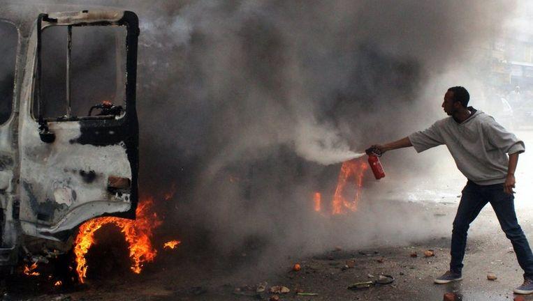 Burgers proberen een politieauto te blussen die tijdens rellen in brand was gestoken. Beeld PHOTO_NEWS