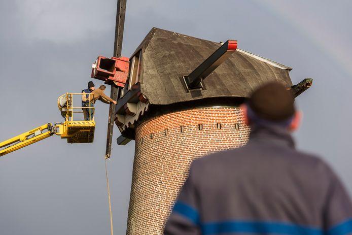 Door middel van een kraan, en onder toeziend oog van de molenaar  worden de wieken tijdelijk verwijderd van de molen in Hapert.