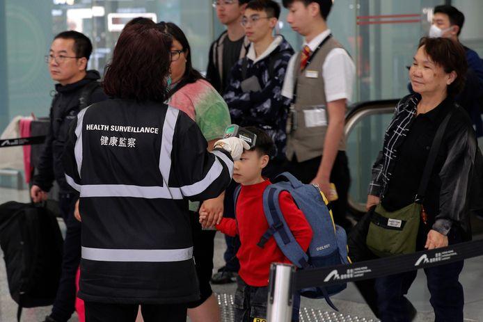 Gezondheidsmedewerkers controleren reizigers op het vliegveld van Hongkong.
