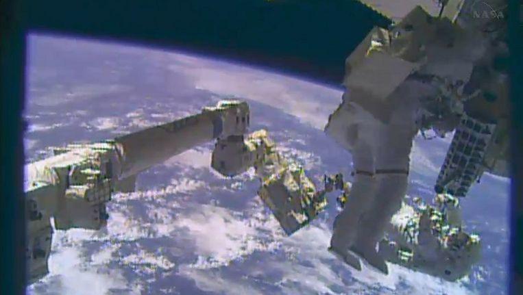 Astronaut Mike Hopkins (rechtsonder) en zijn collega Rick Mastracchio (vooraan) tijdens hun ruimtewandeling vanmiddag. Beeld AFP