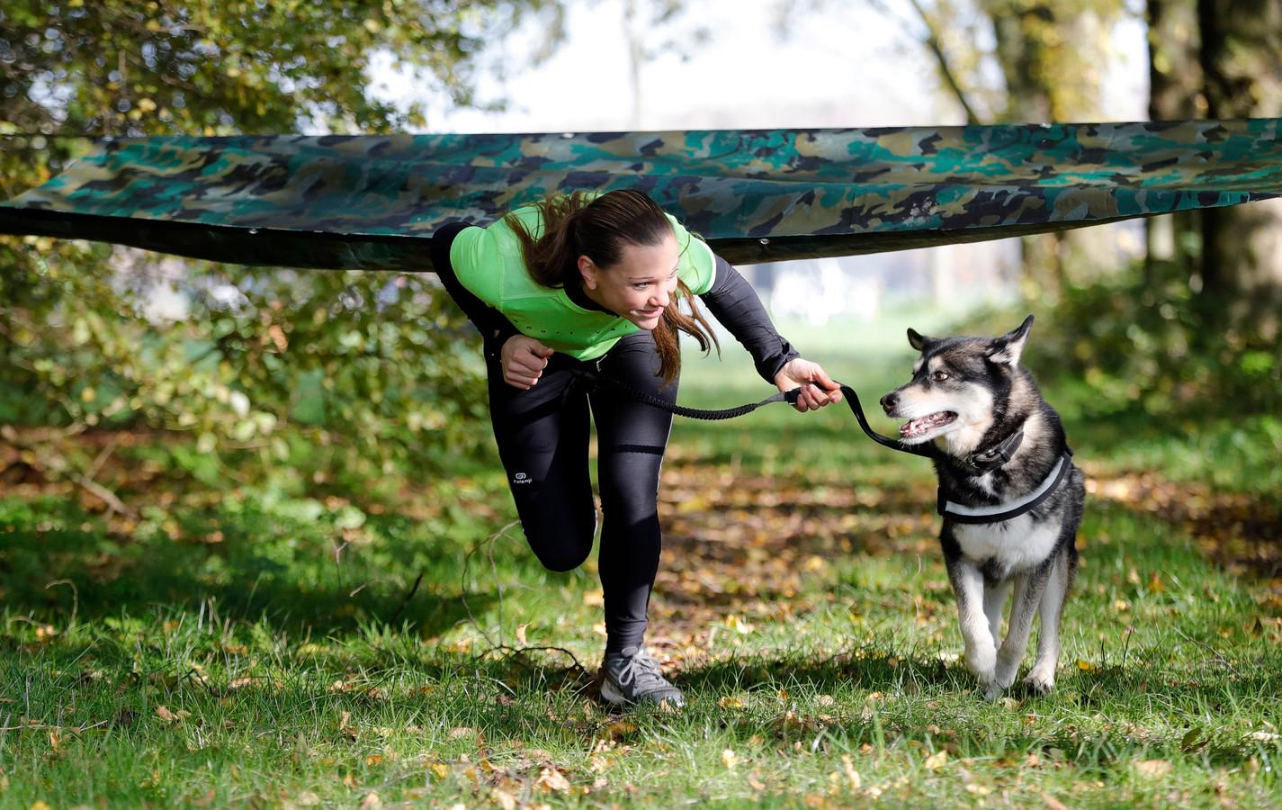 De deelnemers en hun baas rennen in de Dog Fun Survival onder meer onder een in legerkleuren geprint zeil door.