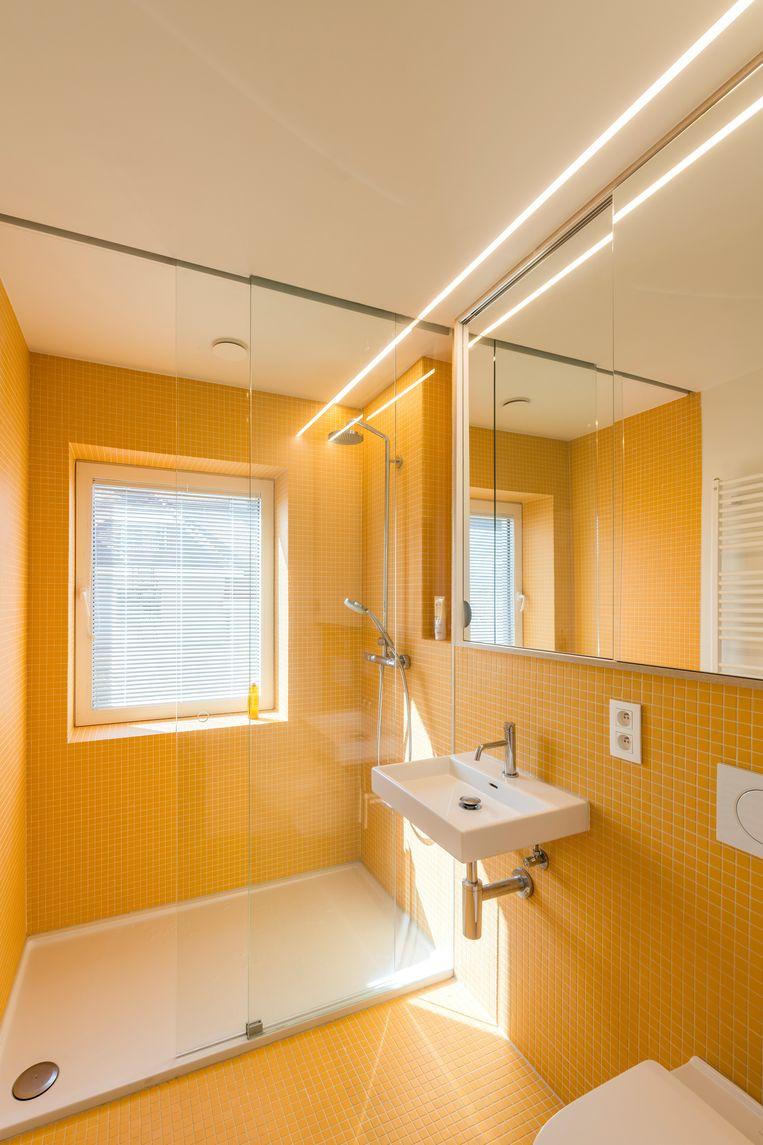 De gele tegels in de badkamer kwamen er na een impulsieve beslissing van de architecten en bewoners.Daar zijn ze nu ontzettend blij mee.  Beeld Luc Roymans