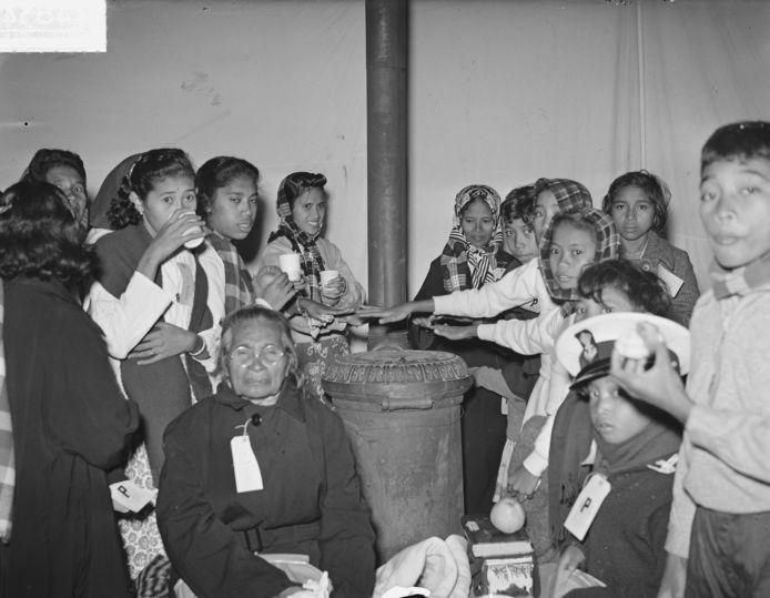 Molukkers warmen zich na aankomst in Nederland in 1951 op bij een kachel.