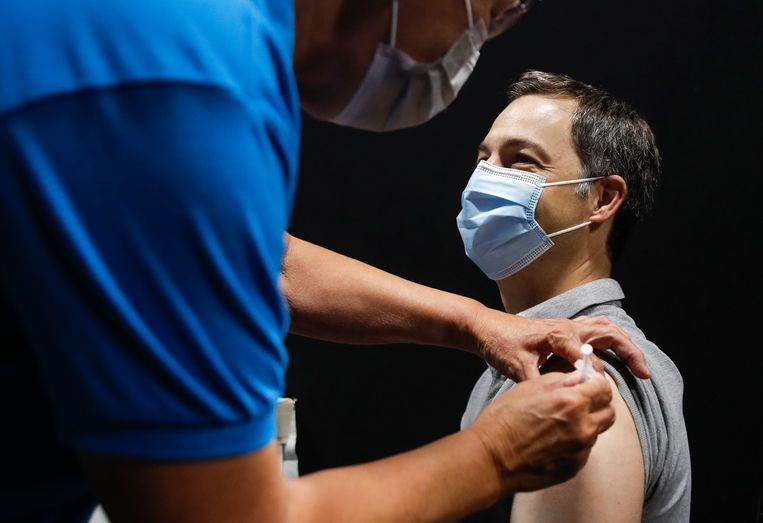 Premier Alexander De Croo krijgt zijn eerste prik in het vaccinatiecentrum van Zottegem. Beeld BELGA