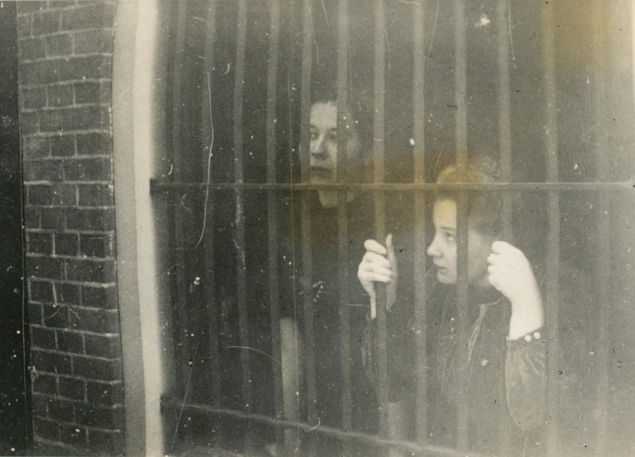 Riet Hoogland en Emmy Naarding, achter de tralies in het politiebureau van Enschede, ca. okt.-nov. 1940