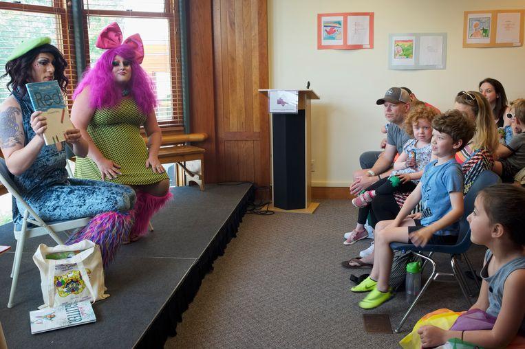 Dragqueens Nikki Champagne en Emoji Nightmare  lezen kinderen voor uit het boek 'Red', over een rood potlood dat van binnen blauw blijkt te zijn.   Beeld Ellen Kok