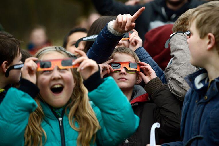 Genkse schoolkinderen genieten met hun eclipsbrilletje van een verduistering in 2015.  Beeld BELGA