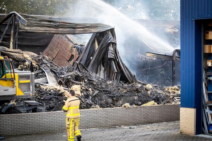 De smeulende resten van de verwoeste loods van Stella Fietsen in Nunspeet.