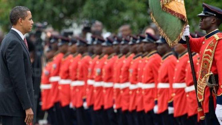 De Amerikaanse president bekijkt de erewachten bij het presidentiële paleis in Accra, Ghana. (AFP) Beeld