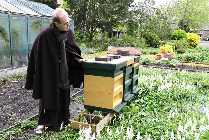 Franciscaner broeder Hans-Peter Bartels ontfermt zich over een drietal bijenkasten achterin de tuin van stadsklooster San Damiano.