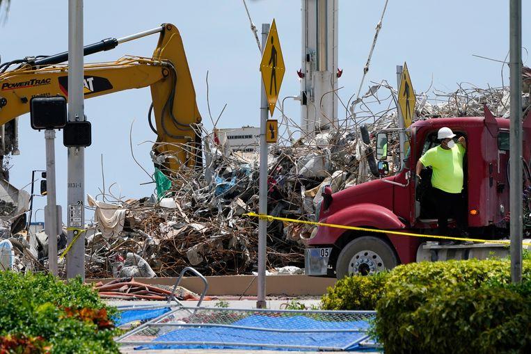 Archiefbeeld. Reddingswerkers en puinruimers werkten zij aan zij op het terrein van de Champlain Towers in Surfside (Miami) in de Amerikaanse deelstaat Florida. (14/07/2021) Beeld AP