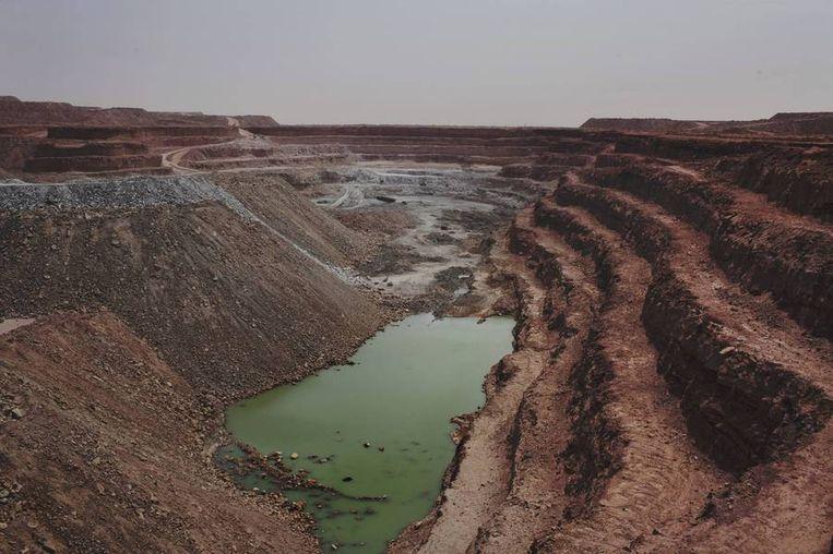 De open 'Tamgak'-mijn. <br /><br />De stad Arlit in Niger is nog niet veel beter geworden van de lucratieve mijnenindustrie daar. Arlit werd in 1969 opgericht na de vondst van uranium, waarna Frankrijk er de mijnenindustrie ontwikkelde. Nu zijn er twee grote uraniummijnen, in Arlit - waar inmiddels zo'n 117.000 mensen wonen - en in het nabijgelegen Akouta.<br /><br />Maar de inwoners van Arlit zelf zijn daar niet veel rijker van geworden. Hun stad, gelegen tussen het Aïr-gebergte en de Sahara, is stoffig en verwaarloosd. Bovendien zijn er, volgens een rapport van Greenpeace, nog steeds te hoge radioactieve stralingen nabij de Nigeriaanse mijnen. Beeld reuters