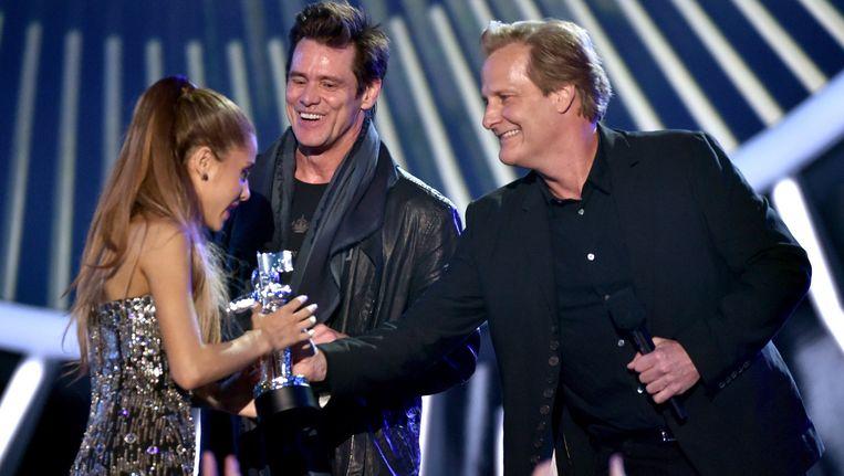 Zangeres Ariana Grande krijgt haar prijs uit handen van acteurs Jim Carrey en Jeff Daniels. Beeld GETTY