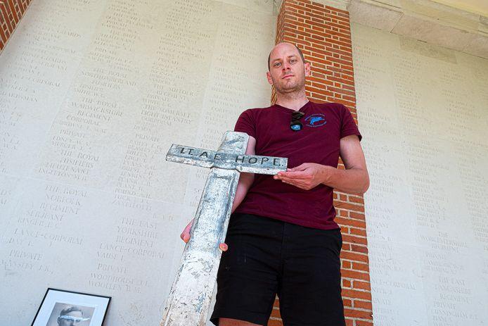 Nico Roelofs met het eerste kruis van luitenant Hope. Die was vermist, maar is gevonden. Niettemin blijft zijn naam op de muur staan.