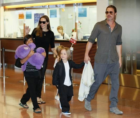 Angelina Jolie (links) en Brad Pitt (rechts) op een vliegveld met hun kinderen Pax Thien, Shiloh en Knox.