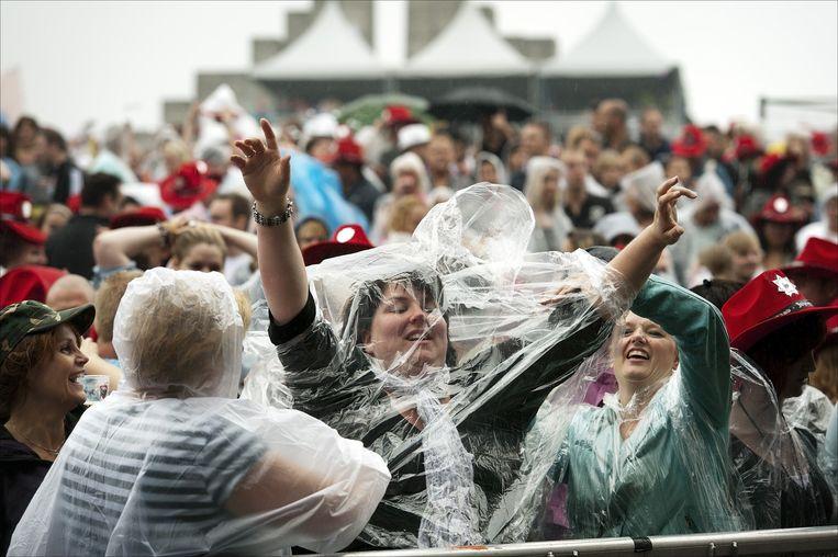 Bezoekers in poncho op een regenachtige editie van dancefestival Dance Valley. Beeld anp