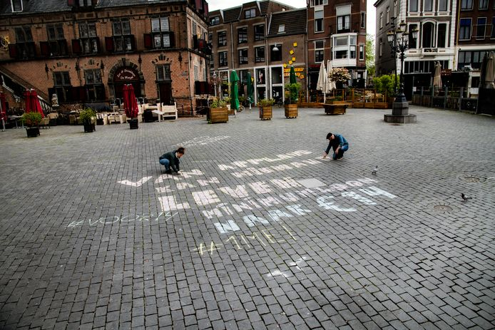 Op de Grote Markt in Nijmegen is met krijt de tekst 'Van applaus kan niemand leven - minimumloon naar €14' geschreven, met de hashtags #voor14 en #1mei'.