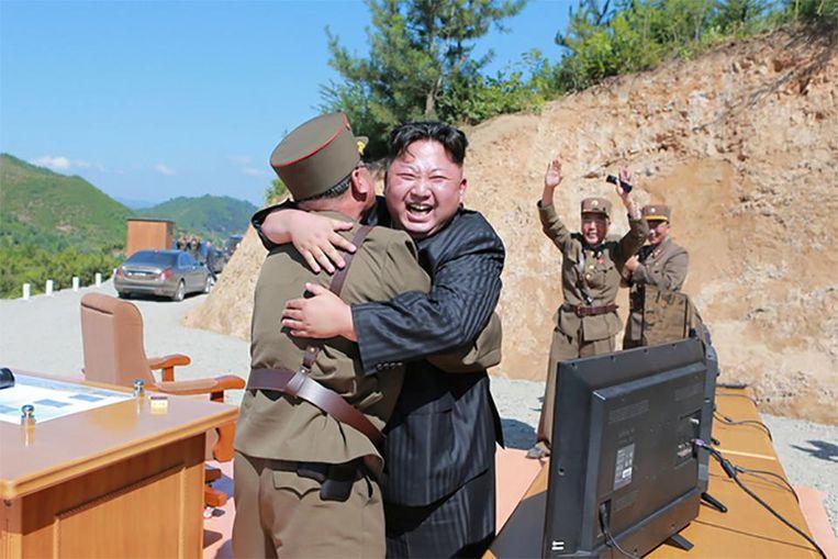 Leider Kim Jong-un knuffelt een van zijn stafleden na de geslaagde rakettest. Beeld reuters