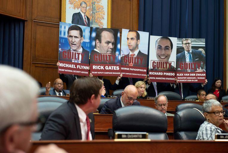 Demonstranten houden posters omhoog met de gezichten van hen die al schuld hebben bekend in het kader van Muellers onderzoek. Beeld AFP