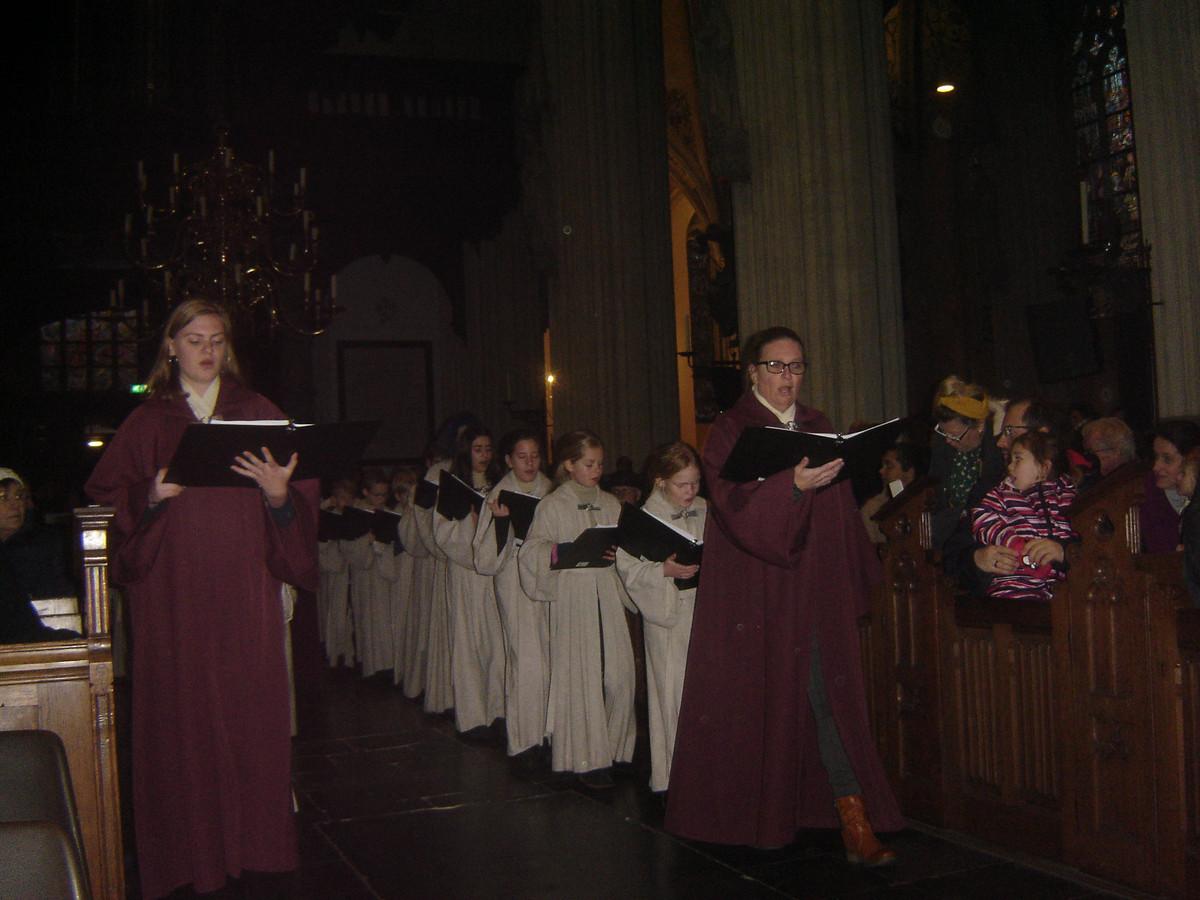 De Schola Cantorum die de Sint-Janskathedraal binnentreedt bij het kerstconcert.