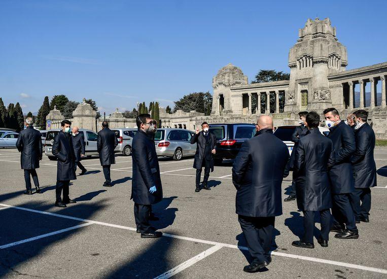 Personeel van begrafenisondernemingen op het plein voor het grote kerkhof in Bergamo. Beeld AP