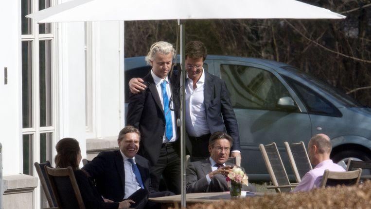 Rutte met zijn arm om PVV-leider Wilders, in aanwezigheid van CDA-leider Verhagen (zittend), en Kamerleden Buma (CDA), Agema (PVV) en Blok (VVD) op een van de dagen van onderhandelingen in het Catshuis. Beeld anp