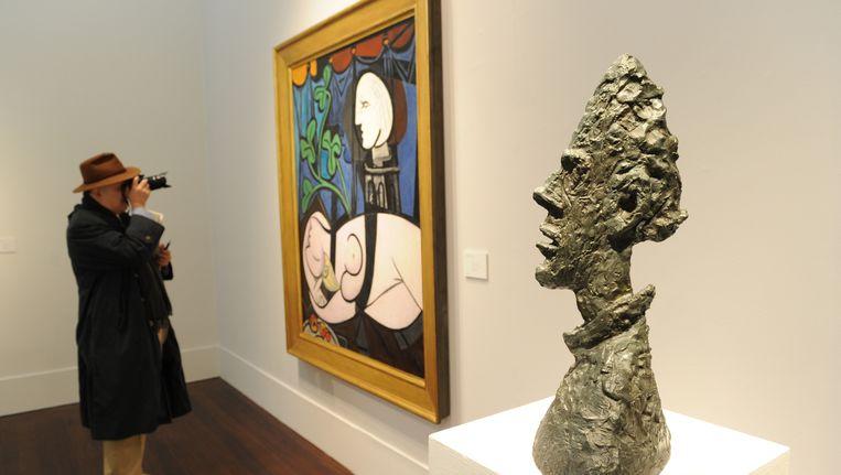 Het bronzen beeld van Giacometti (rechts op de voorgrond) werd voor 50 miljoen dollar verkocht. Beeld AFP