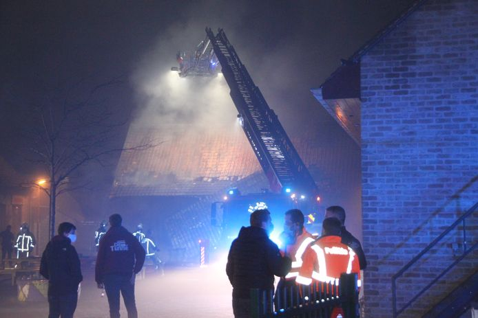 Vanop een ladderwagen werd de brand aan de voorkant van het jeugdhuis bestreden. Burgemeester Bert Maertens overlegt op de voorgrond met de politie.