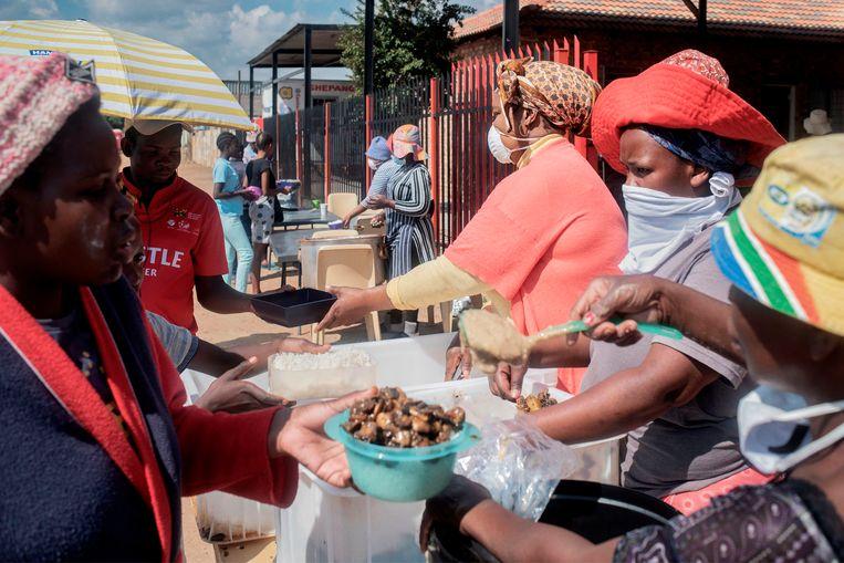 Voedselbedeling in de sloppenwijk Tembisa, Johannesburg. President Ramaphosa heeft een coronahulppakket van liefst 24 miljard euro aangekondigd. Miljoenen armen krijgen de komende maanden extra uitkeringen. Beeld AFP