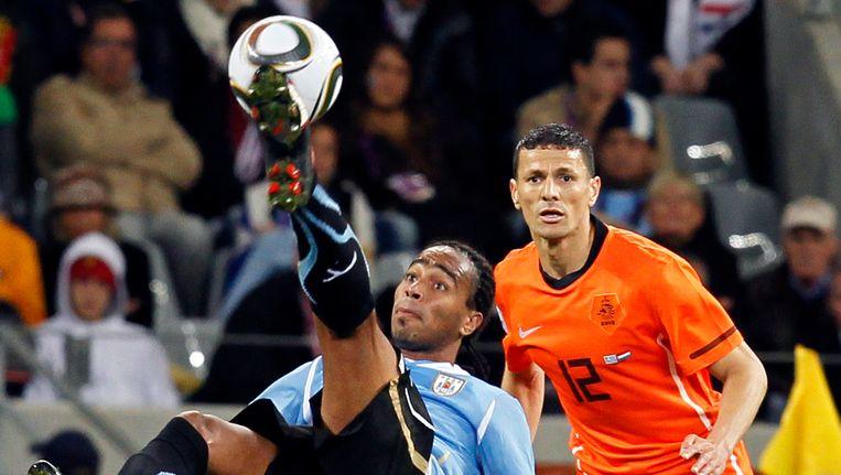 Khalid Boulahrouz kijkt naar de omhaal van Alvaro Pereira tijdens de halve finale van het WK 2010 in Zuid-Afrika. Nederland verloor later de finale met 1-0 tegen Spanje. Beeld AP