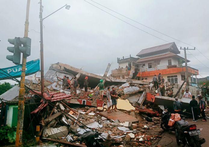 Bewoners te midden van hun verwoeste huizen in Mamuju in West-Sulawesi, Indonesië.
