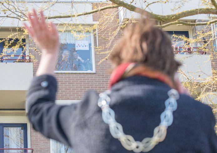 Burgemeester van Goes Margo Mulder zwaait naar de 107-jarige Aaltje Paulusse-Priester achter het raam van haar appartement.