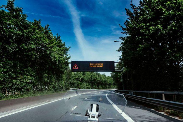 Een paneel op de autosnelweg in de buurt van Brussel waarschuwt: 'Geen onnodige verplaatsingen'. Beeld © Stefaan Temmerman