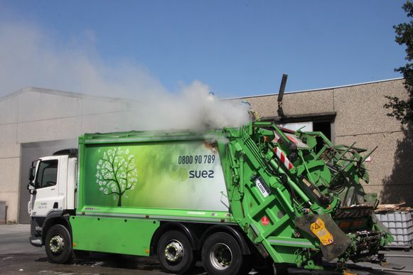Brandweermannen kropen op de vuilniswagen om te blussen.