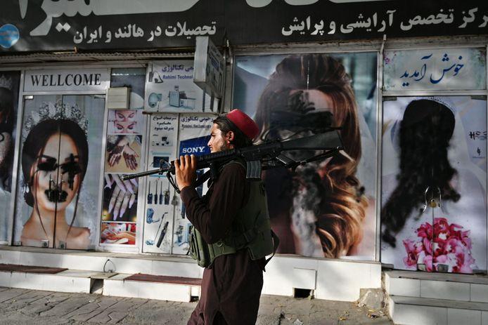 Een talibanstrijder wandelt in hoofdstad Kaboel voorbij een schoonheidssalon waarvan de foto's van vrouwen zijn overspoten met zwarte spray.