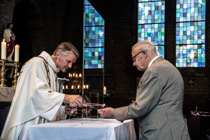 Zo gaat het vanwege corona in veel rk-kerken in Nederland: ter communie gaan met een spatscherm ertussen. Totdat de bisschoppen met nieuwe richtlijnen komen, blijft het zo. (Deze foto is niet in de regio Moerdijk/Etten-Leur gemaakt.)