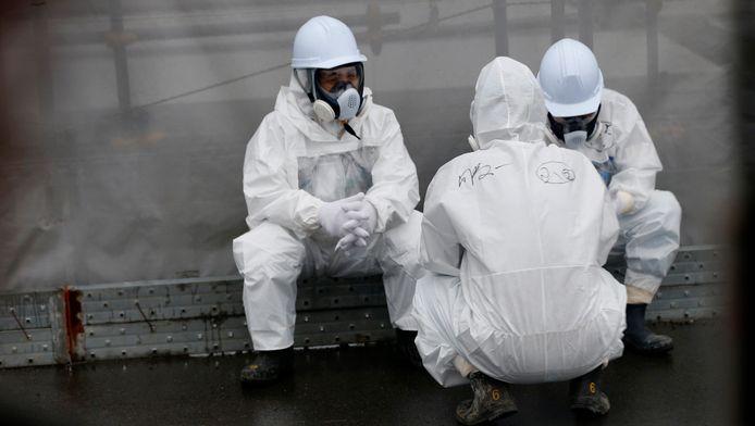 Werkers in beschermende kledij in de kerncentrale van Fukushima