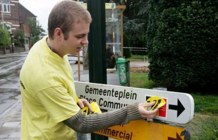 Manifestanten van Vlaams Belang plakten stickers over Belgische vlaggen. Beeld UNKNOWN