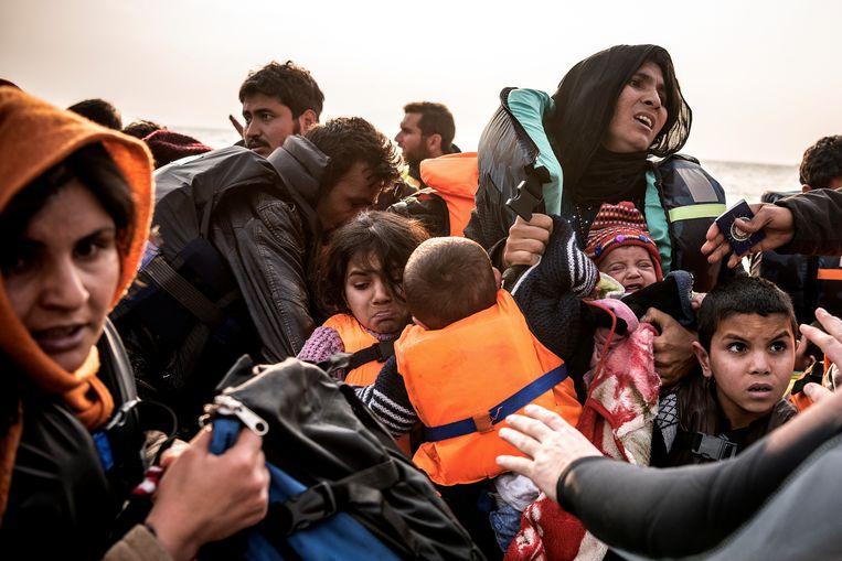 Voor de kust van het Griekse eiland Lesbos worden in maart 2016 migranten van een boot gehaald. Beeld Sergey Ponomarev/The New York Times