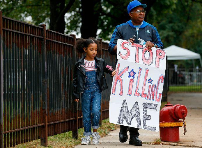 Een opa en zijn kleindochter betogen bij het gerechtsgebouw in Chicago waar politieagent Jason Van Dyke terechtstaat voor de moord op de zwarte tiener Laquan McDonald.