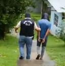 Een van de twee verdachten wordt weggevoerd na zijn arrestatie.
