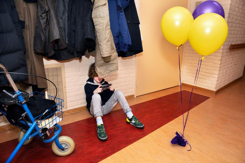 Jan (6) in Arnhem, op de telefoon van zijn vader. Hij kijkt het liefst filmpjes van vlogger Dylan Haegens. Beeld Martijn van de Griendt