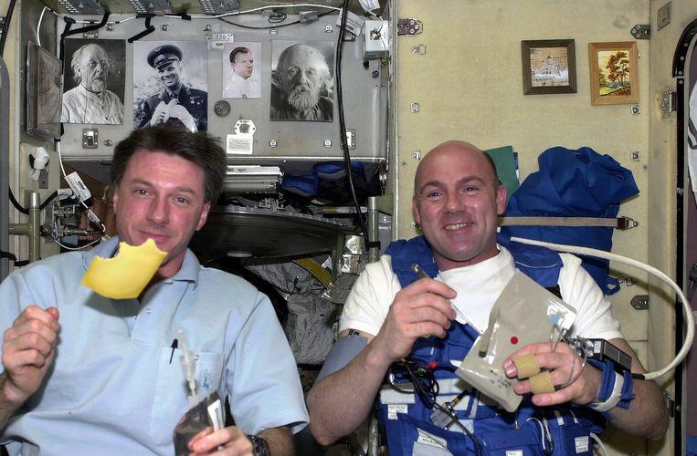Astronauten André Kuipers en Michael Foale eten kaas als ontbijt in de ruimte.  Beeld EPA/ESA